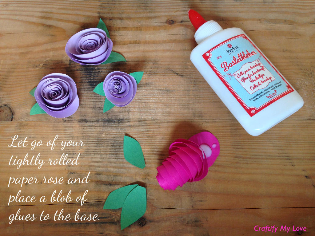 This image shows how to make paper roses - step 2: let go of your tightly rolled spiral and place glue on the base.