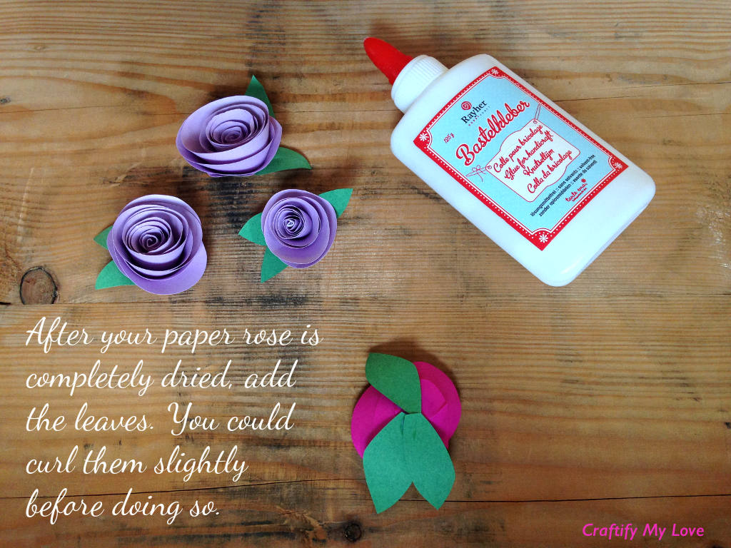This image shows how to make paper roses - step 4: After the rose is dry, add the leaves. You can curl them slightly before doing so.