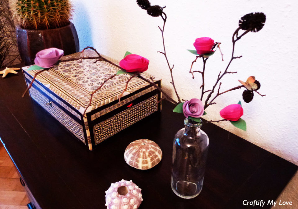 This image shows an ever blooming diy paper rose bush made out of pink, violet and green construction paper.