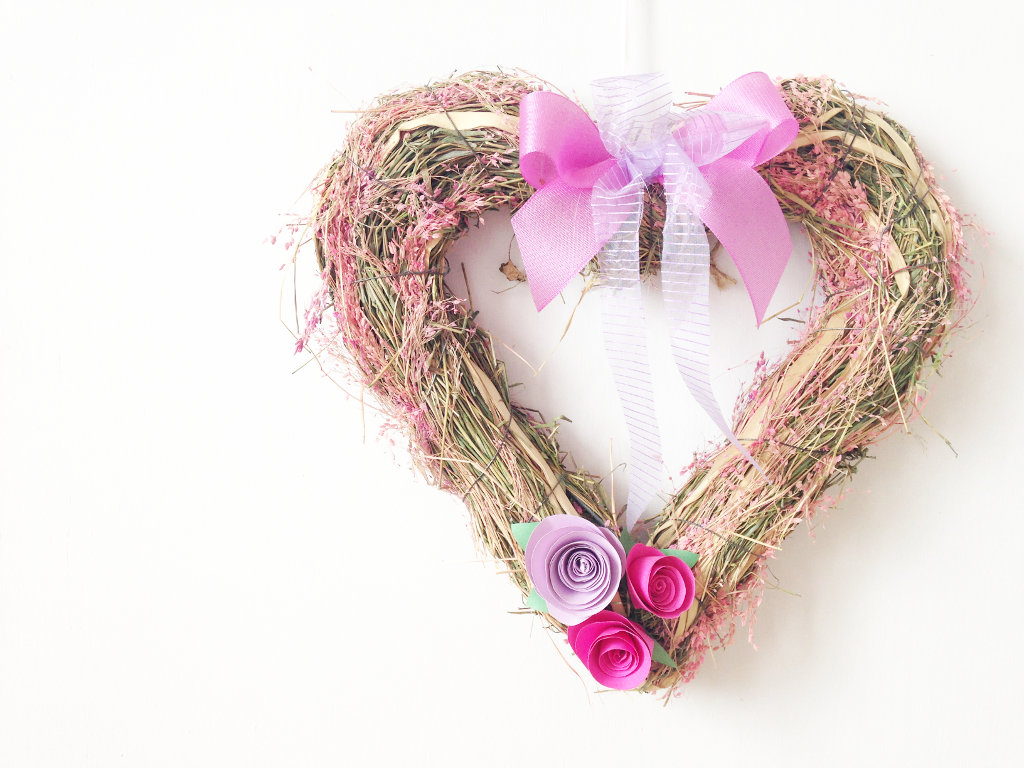 This image shows a DIY pink and lavender heart-shaped spring wreath with paper roses and ribbon bow