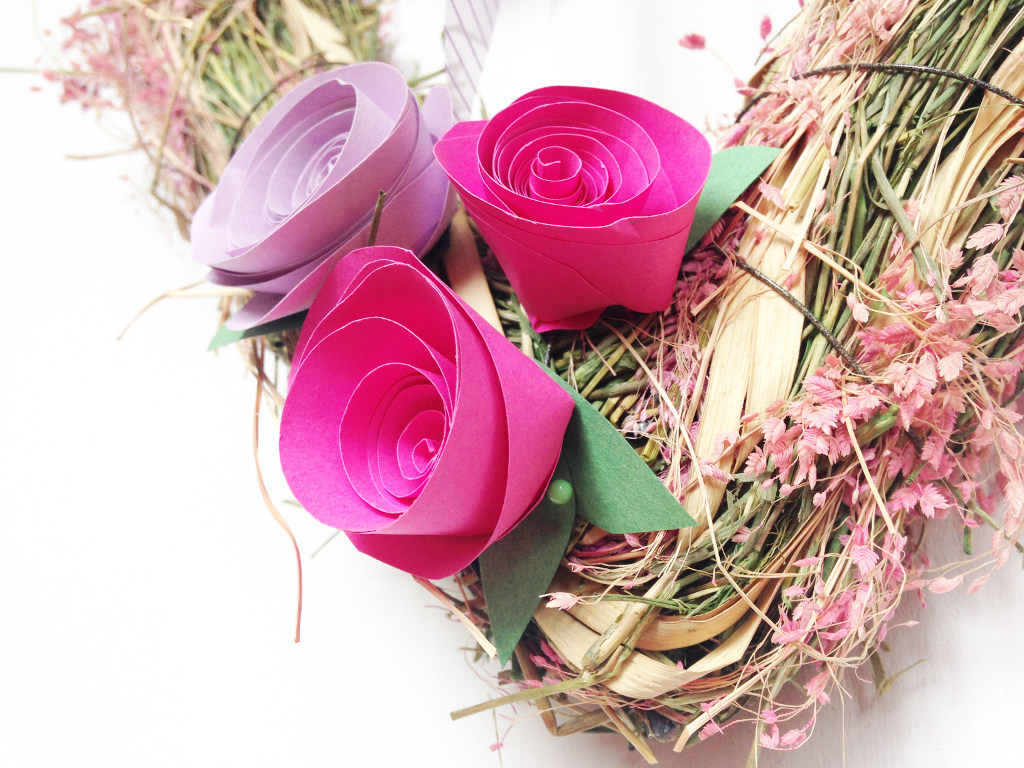 This image shows paper roses being fixed to a spring wreath in pink and lavender