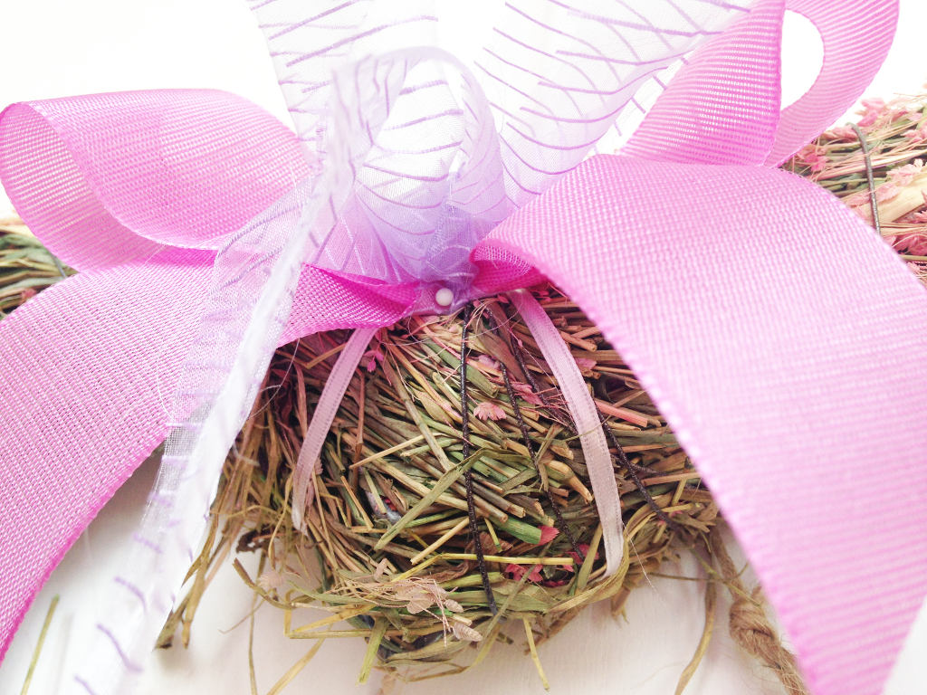 this image shows a pink and violet DIY ribbon bow attached to a straw spring wreath