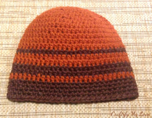 Crocheted men's hat in brown and rust stripes.