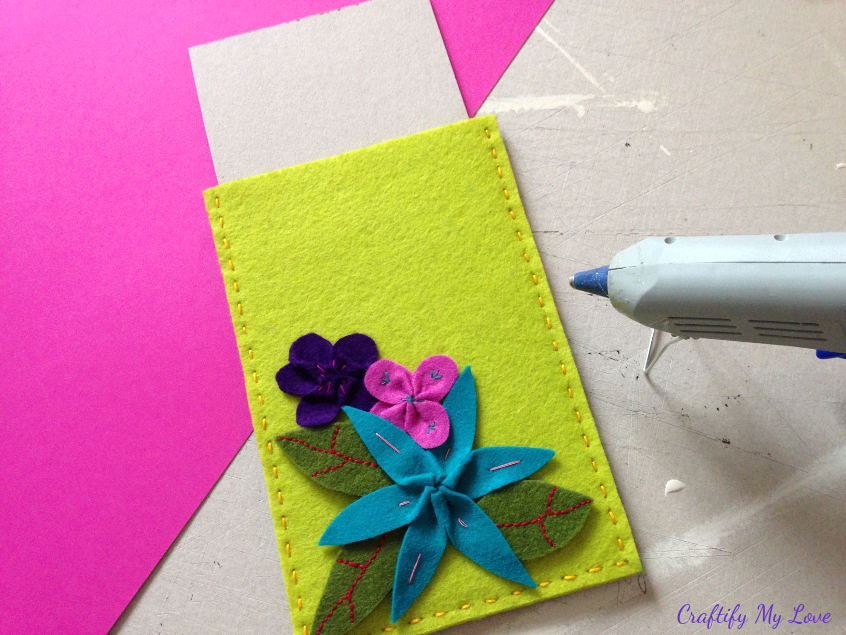 placing cardboard in hand sewn tablet sleeve before using hot glue to add felt flowers and leaves