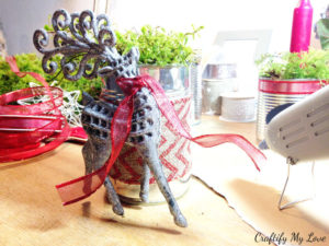 hotgluing dollar tree reindeer to recycled tin can DIY