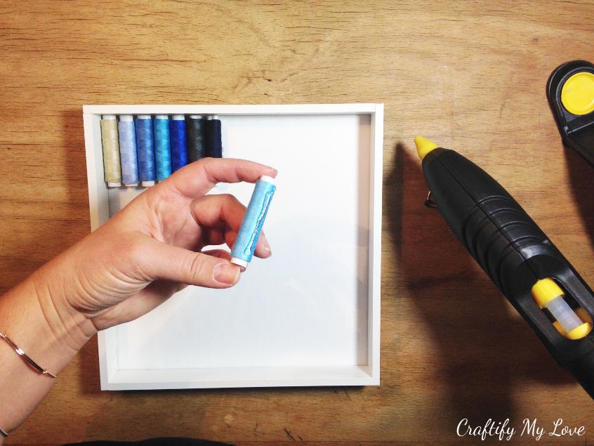 hotgluing spools or bobbins into IKEA RIBBA frame