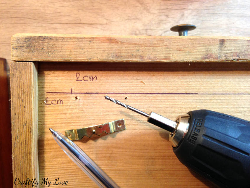 predrilling holes to fix sawtooth hanger to recycled drawer. This prevents wood from splintering.