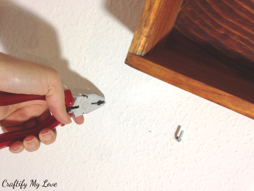 screwing hooks into wall for DIY decor storage project