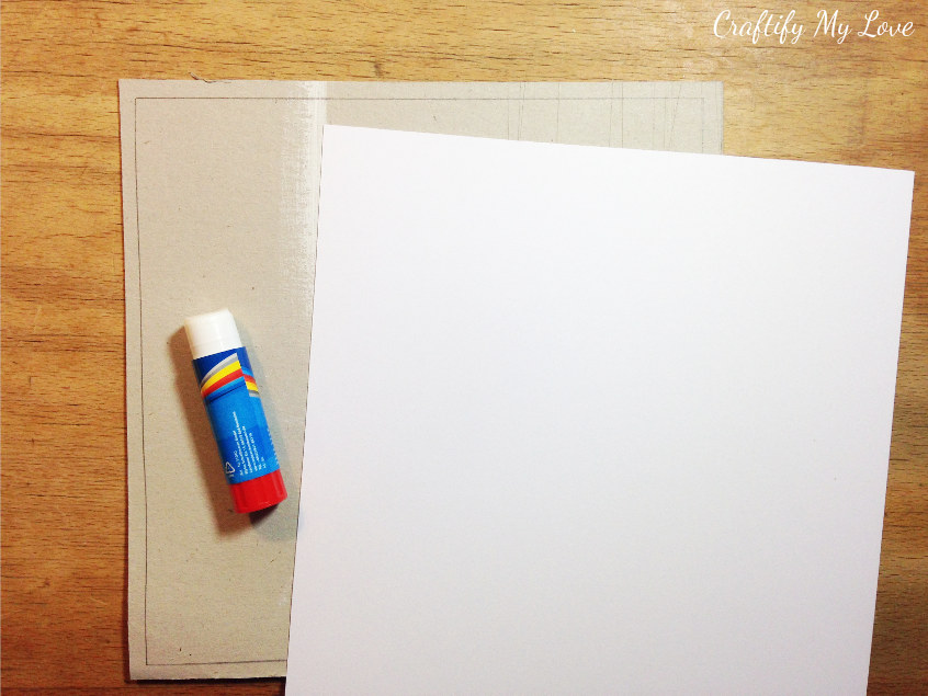covering cardboard with white yardstick as base for melted crayons crafting inspired wall art