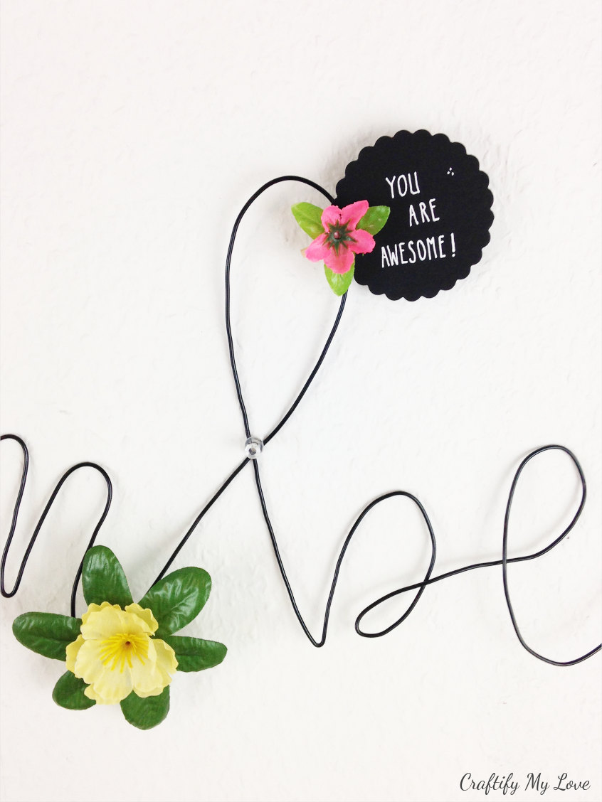 motivational quote pinned with a floral peg to wire memo board