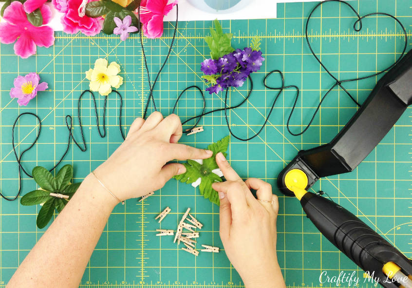 gluing faux leaves on silk flower to make spring flower memo pin that also works great for gift wrapping