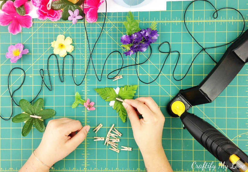 hot gluing tiny wooden clothespins to silk flowers to create reusable commando centre decor