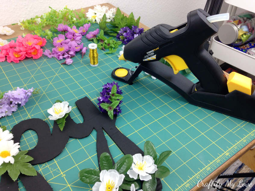 hotgluing flowers to chalkpaint covered cardboard sign