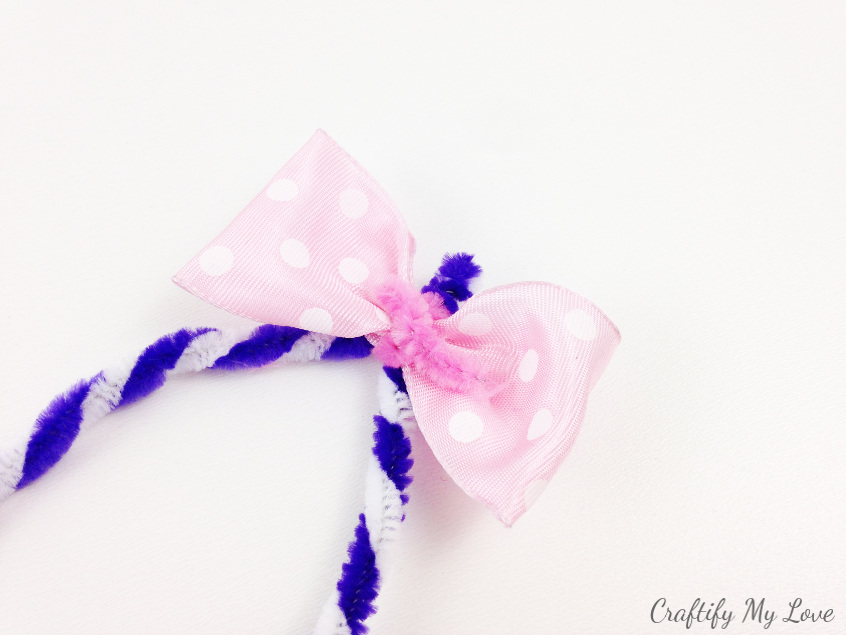 fix a pink ribbon bow to your bunny ears using a pipe cleaner