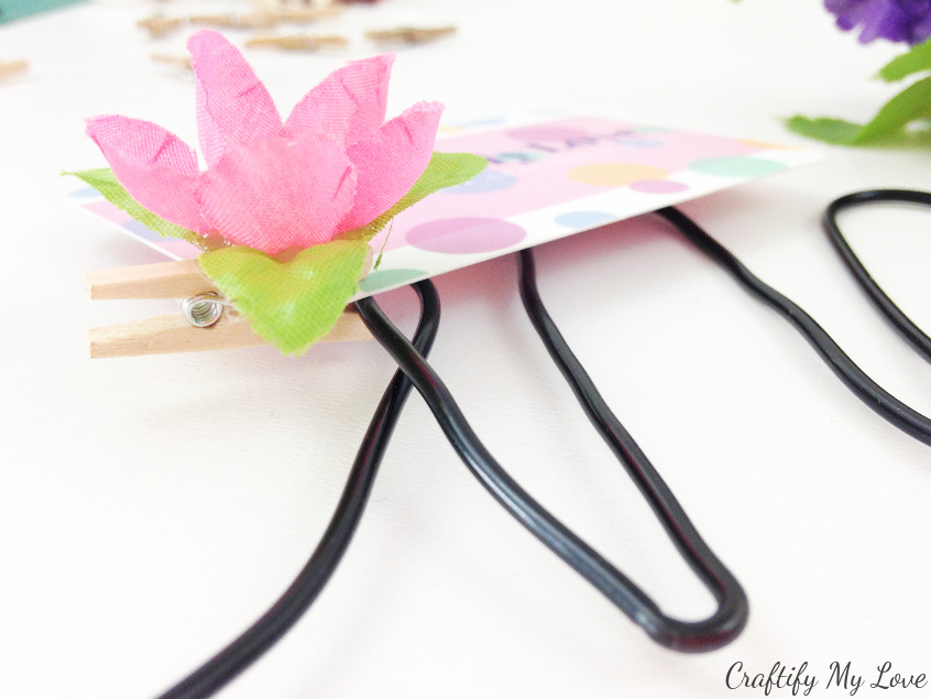 business card pinned to white board with a decorative flower pin