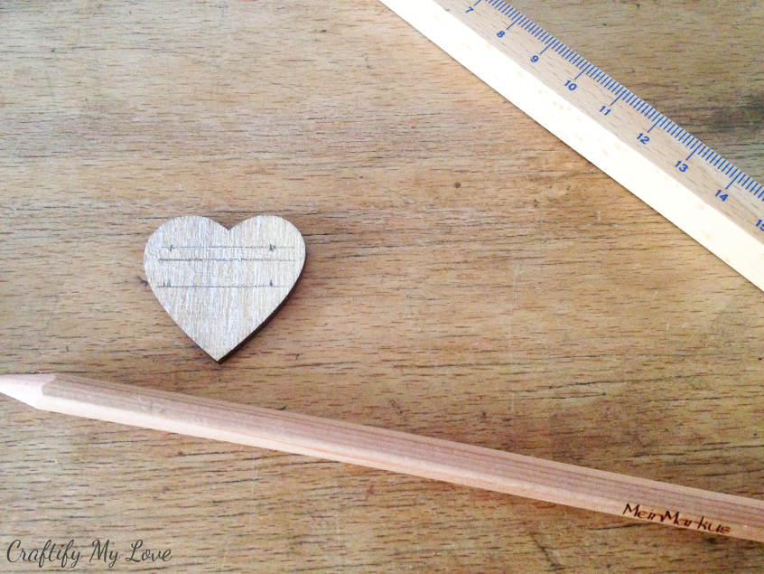preparing little wooden hearts for DIY herb markers hand labeled