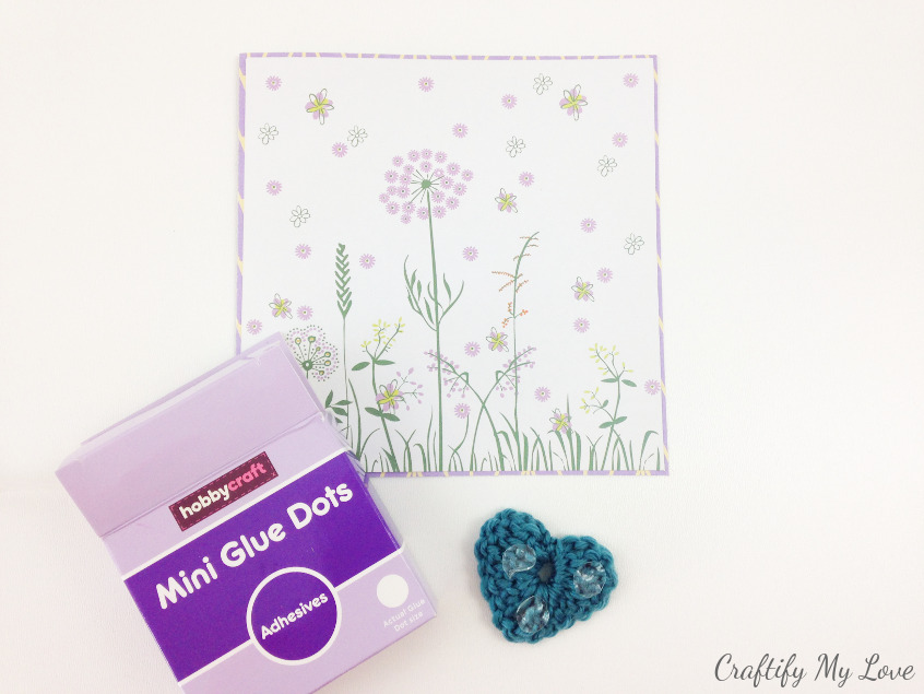 using glue dots to stick crocheted heart to handmade paper mother's day card