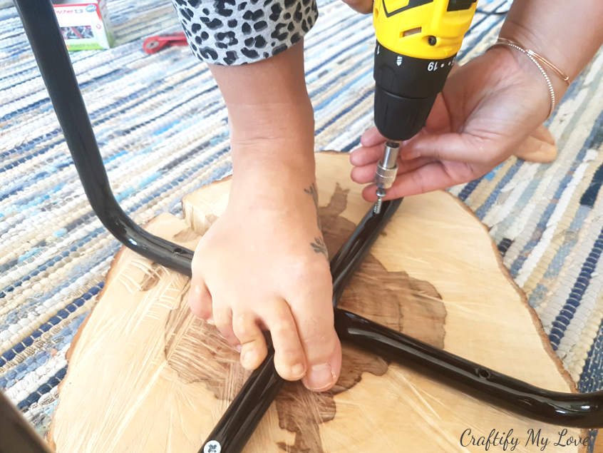 holding stool legs in place when using your drill and screws to fasten them to the natural wood handmade table