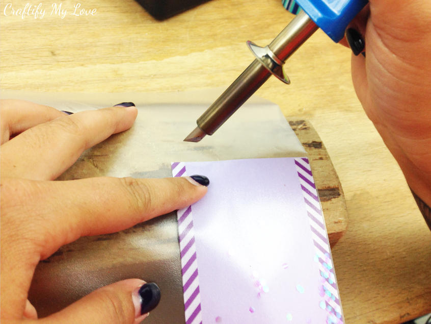 using a dremel or a fuse to seal the glitter sequins into foil in this kids craft bookmark project