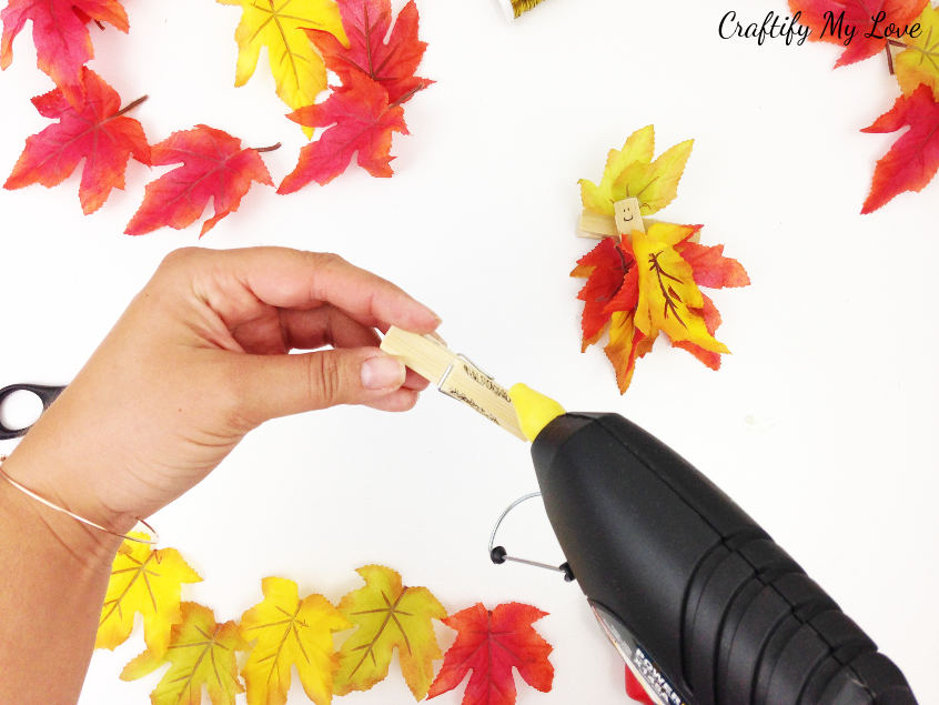 adding hot glue to apply autumn foliage to clothespin upcycling fairy craft