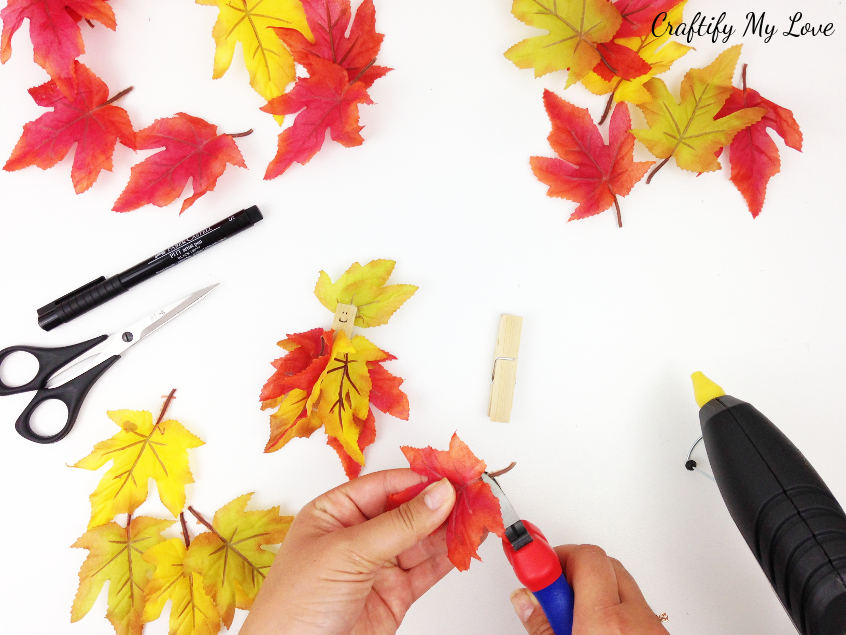 clipping off the stems of faux fall leaves for a fair craft that is suitable for kids and adults alike