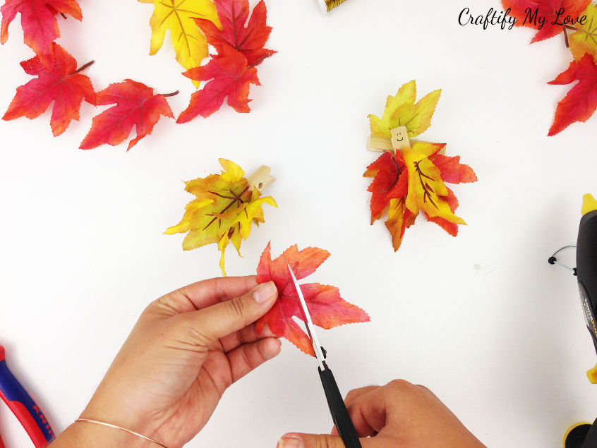 cutting silk autumn leaf to size to create a darling fall fairy hat