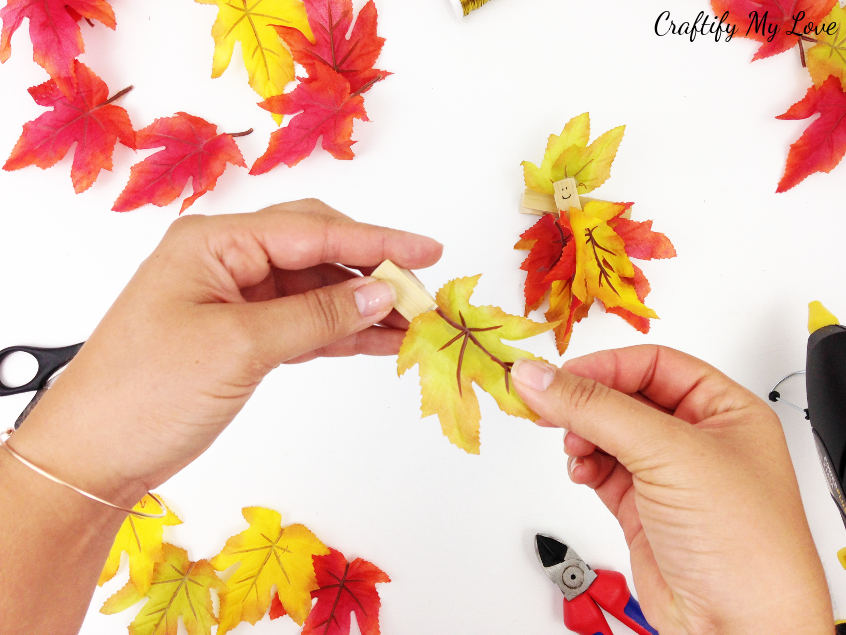 gluing faux fall leaf to clothes pin for fall kids craft project that can also be made as a flower fairy