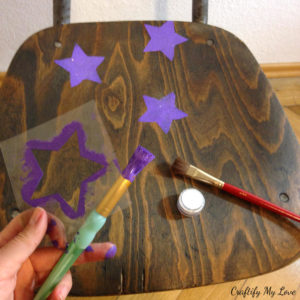 stenciling purple glitter stars to old school chair with a handmade plastic stencil