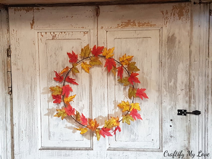 delicate and simple fall wreath DIY using single faux maple leaves and gold wire.