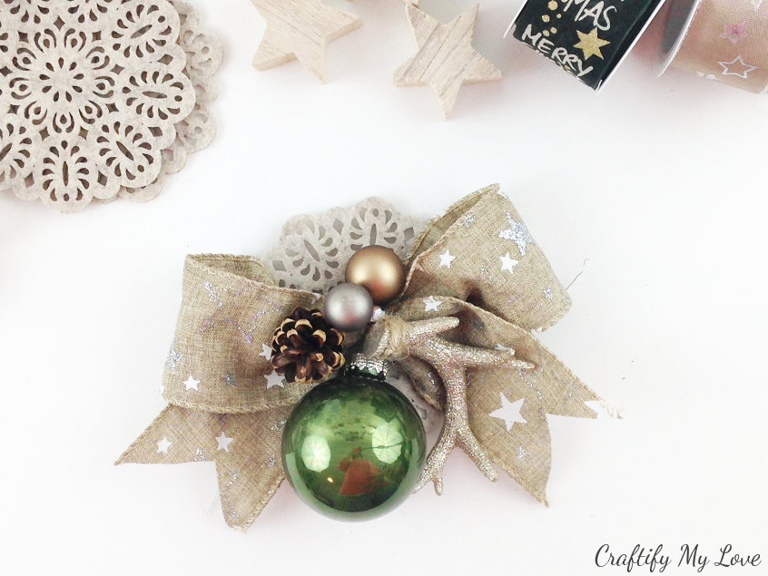 Burlap ribbon bow decorated with antlers, pine cones, christmas bulbs and a felt coaster