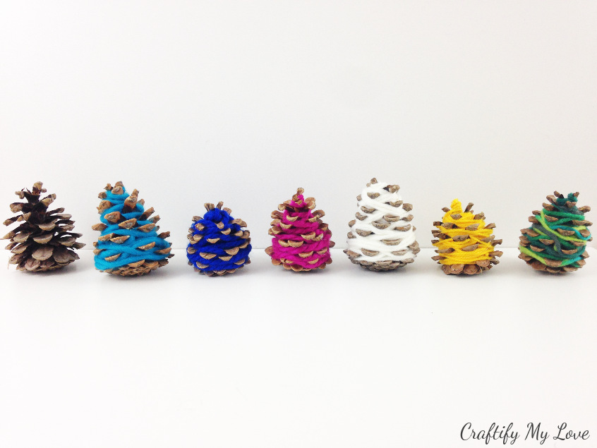 colourful pine cone yarn Christmas trees that are a frugal home decor that you can craft with your kids