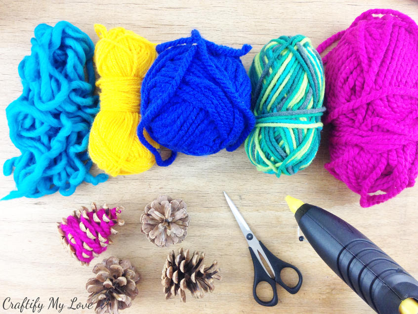 supplies for decorative hygge mini Christmas trees are yarn scraps and pine cones