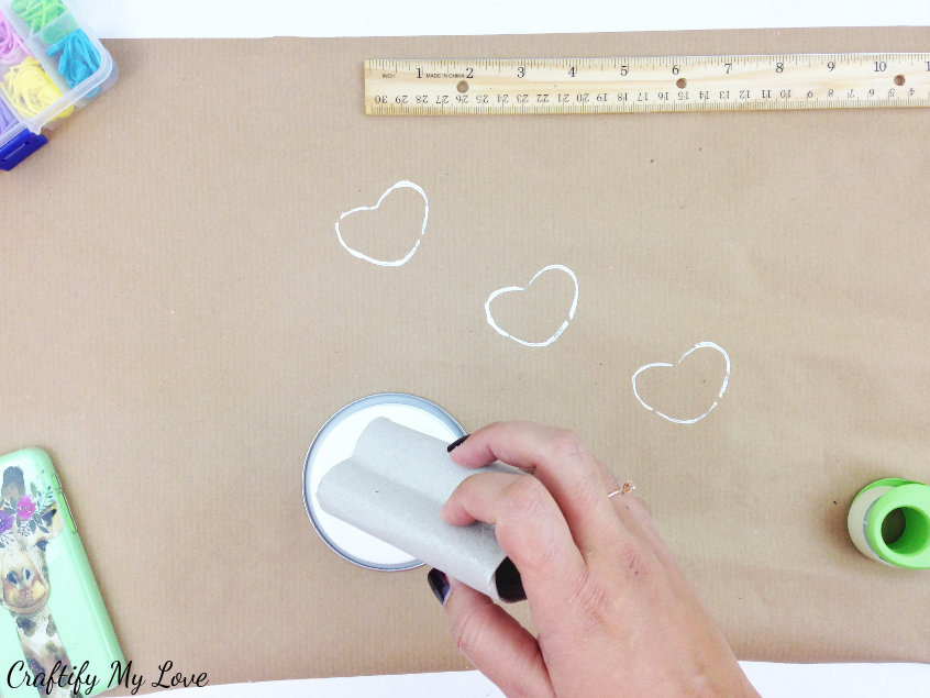 dip the heart shaped tp roll into paint to hand print Valentine's Days hearts on your DIY wrapping paper made from brown paper
