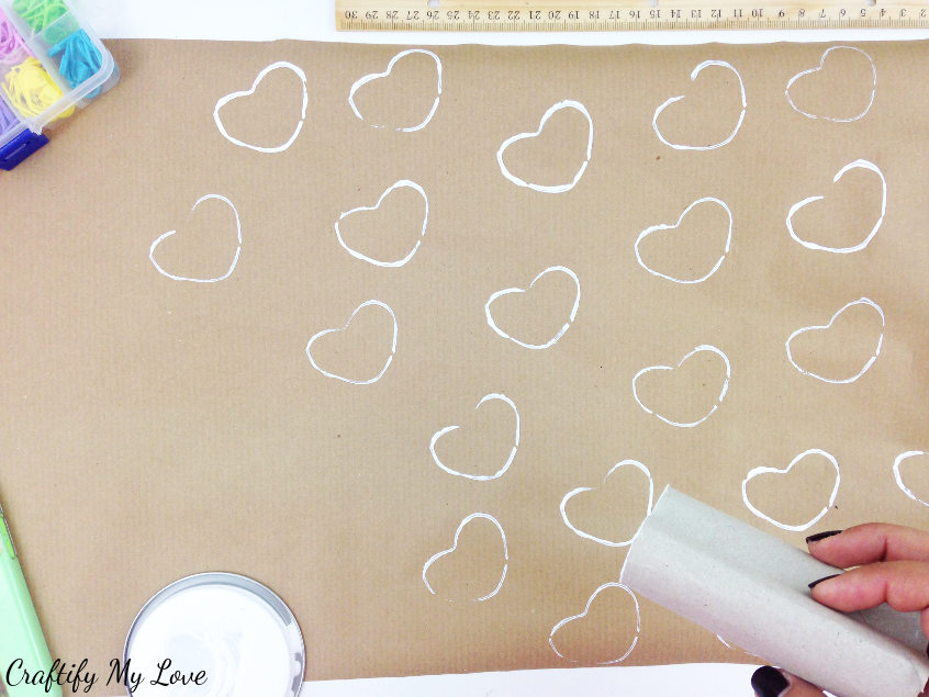 Repeatedly stamp your DIY template and create a pattern on the shipping paper to make a brown paper gift wrap idea