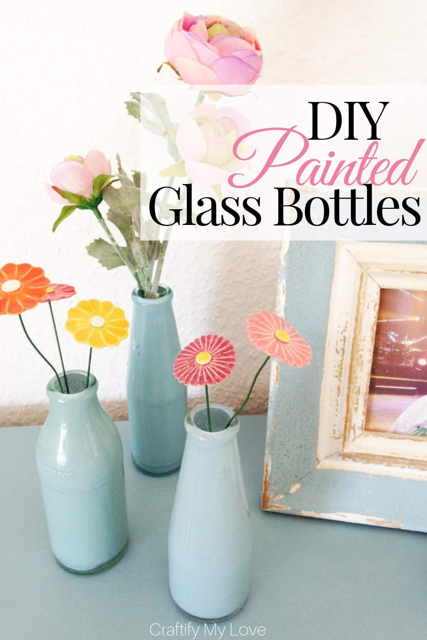 Here's a fun recycling craft for you: DIY upcycled painted glass bottles turned inside out painted little vases. They are quick & easy to make and are the perfect frugal home decor to decorate your table with. #craftifymylove #upcyclingcraft #paintedglassbottles #DIYpaintedvases #frugalhomedecor #DIYhomedecor #mothersday #tablesetting