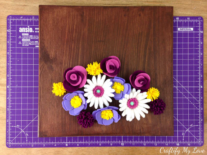 arrange prepared diy felt flowers on wood sign to come up with your design idea