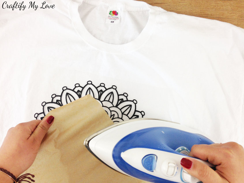 ironing the mandala design on your DIY creative t-shirt idea by using iron on vinyl, baking sheet and an iron