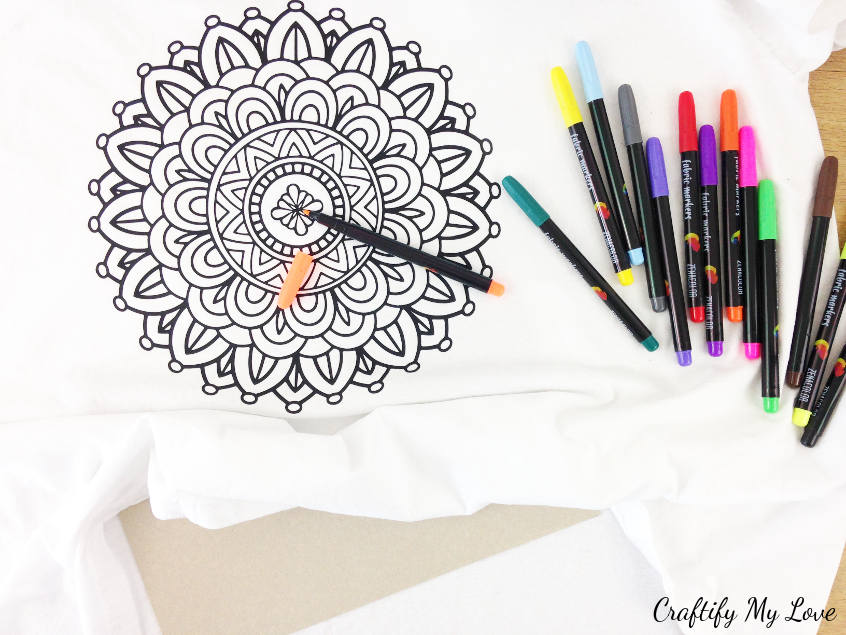 start filling in or colouring the mandala design using fabric markers to create a unique kids t-shirt as a summer activity for a rainy day